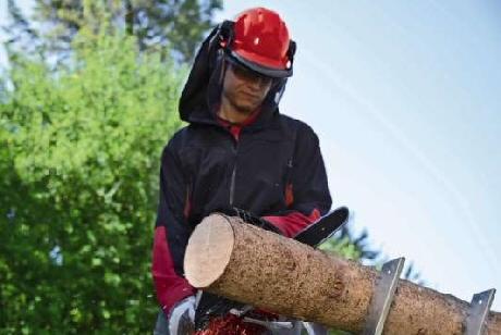 Einhell Petrol Chainsaw cuttinga log with a metal sawhorse